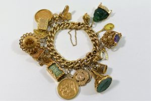 A 15 carat gold curb link charm bracelet, the clasp stamped '15CT', with 23 yellow metal charms, combined weight 100.2g  SOLD - £1,280