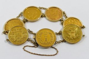 A yellow metal bracelet with seven gold coins in removeable pendant mounts SOLD - £1,350