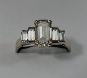 An Art Deco style white gold diamond five stone ring, the centre emerlad-cut diamond approximately 1.3 carats Estimate £2000 - £3,000